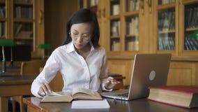 A mulher bonita está usando o portátil, livro de leitura que senta-se na tabela na biblioteca filme