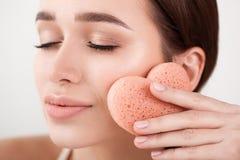 A mulher bonita faz um tratamento facial com uma esponja fotografia de stock