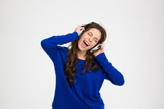 Mulher bonita feliz nos fones de ouvido que escuta a música e que canta Foto de Stock Royalty Free