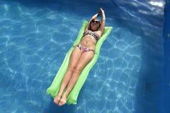 A mulher bonita feliz nova no encontro do biquini e dos óculos de sol relaxa no colchão de ar do flutuador na piscina do recurso  Foto de Stock
