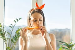 Mulher bonita feliz nova que come a fatia alaranjada em casa perto da janela fotos de stock royalty free