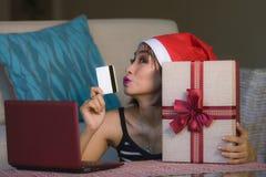 A mulher bonita feliz nova relaxou em casa o sofá no chapéu de Santa usando o laptop que paga o presente de Natal com o SMI do ca foto de stock