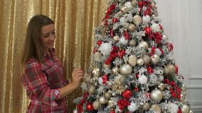 Mulher bonita feliz que decora a árvore de Natal