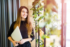 Mulher bonita feliz que está na parede do escritório com caderno Ilustração do JPG + do vetor Foto de Stock