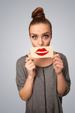 Mulher bonita feliz que guarda o cartão com marca do batom do beijo Foto de Stock