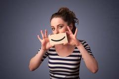 Mulher bonita feliz que guardara o cartão com smiley engraçado Fotografia de Stock Royalty Free