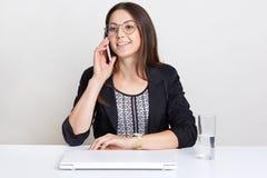 A mulher bonita feliz recebe a notícia positiva através do telefone celular, tem a conversação com o colega, vestido na roupa for fotografia de stock