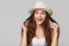 Mulher bonita feliz surpreendida que olha lateralmente no excitamento, isolado no fundo cinzento foto de stock