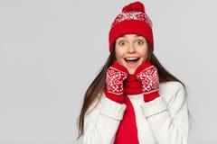 Mulher bonita feliz surpreendida que olha lateralmente no excitamento Menina do Natal que veste o chapéu feito malha e os mitenes fotos de stock