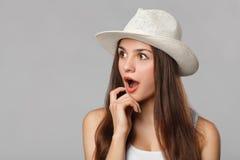 Mulher bonita feliz surpreendida que olha lateralmente nos excitemen, isolados no fundo cinzento foto de stock royalty free