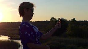 A mulher bonita gerencie um spinnet no por do sol vídeos de arquivo