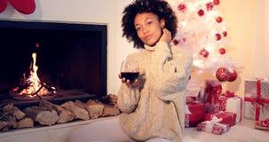 A mulher bonita guarda o vidro de vinho ao lado da chaminé foto de stock royalty free
