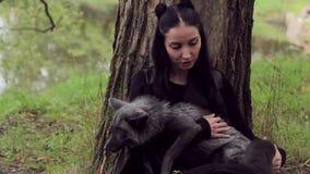 A mulher bonita guarda um verão da raposa preta a árvore filme