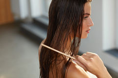 Mulher bonita Hairbrushing seu cabelo molhado longo Cuidados capilares imagem de stock royalty free