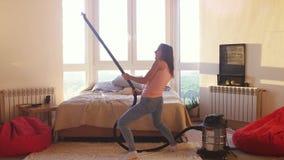 A mulher bonita hoovering o assoalho em casa que usa o aspirador de p30 moderno e que escuta a música e a dança housework filme