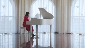 A mulher bonita joga um piano branco video estoque