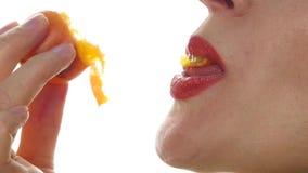A mulher bonita lambe e comendo o pêssego em um fundo branco a menina do close-up morde um pêssego Movimento lento video estoque