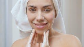 A mulher bonita limpa a cara com o gel para a lavagem facial vídeos de arquivo