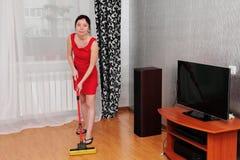 A mulher bonita limpa a sala Fotos de Stock
