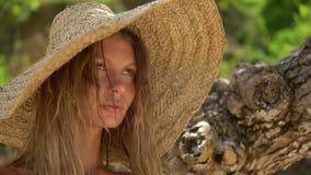 A mulher bonita loura anda na praia, veste o chapéu de palha filme