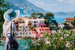 Mulher bonita loura no chapéu azul do sol e na roupa branca que aprecia a vista de casas tranquilos coloridas de Assos da vila em foto de stock