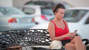 Mulher bonita madura do turista que usa o telefone ao sentar-se no banco video estoque