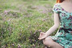 A mulher bonita medita no parque Fotos de Stock Royalty Free