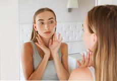 Mulher bonita, menina que tocam em seu pescoço ao olhar no espelho, beleza e conceito da forma, enrugamentos fotografia de stock