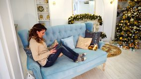 A mulher bonita moderna senta-se no Internet e nos rolos nas notícias da tabuleta, sentando-se no sofá azul na sala festiva decor video estoque