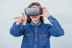 A mulher bonita moreno que levanta no estúdio, calças de brim vestindo veste, usando auriculares da realidade virtual dos VR-vidr fotos de stock royalty free
