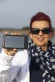 A mulher bonita mostra a telefone a exposição vazia Fotografia de Stock Royalty Free