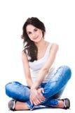 Mulher bonita na calças de ganga que senta-se no assoalho branco Imagem de Stock