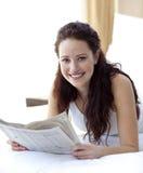 Mulher bonita na cama que lê um jornal Foto de Stock Royalty Free