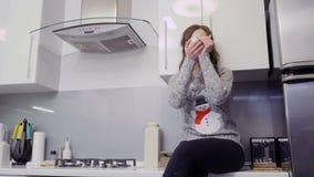 A mulher bonita na camiseta morna bebe o chá na cozinha filme
