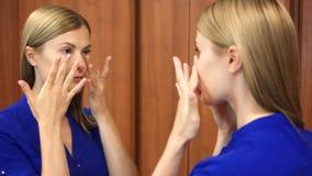 Mulher bonita na obscuridade - blusa azul que prepara-se para a data que verifica a roupa e cara no espelho video estoque