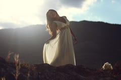 Mulher bonita na parte superior da montanha na luz do por do sol Fotos de Stock
