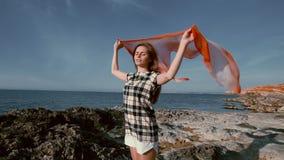 Mulher bonita na praia perto do mar com um lenço no vento video estoque