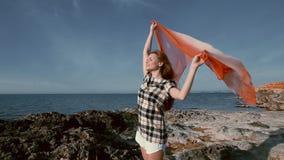 Mulher bonita na praia perto do mar com um lenço no vento vídeos de arquivo