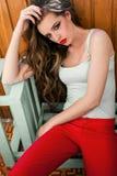 Mulher bonita na roupa colorida no assento vermelho das calças Imagem de Stock Royalty Free