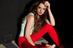 Mulher bonita na roupa colorida no assento vermelho das calças Imagem de Stock
