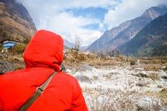 Mulher bonita nepalesa superior ativa no revestimento vermelho do inverno que examina o fundo da montanha e do céu azul Espera de imagem de stock royalty free