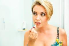 Mulher bonita no banheiro que aplica o batom foto de stock royalty free