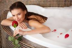A mulher bonita no banho com aumentou Cuidado do corpo foto de stock