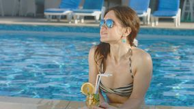 A mulher bonita no biquini, óculos de sol aprecia o cocktail, festa na piscina video estoque