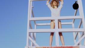 Mulher bonita no biquini que está na estação da salva-vidas, torre da salva-vidas video estoque