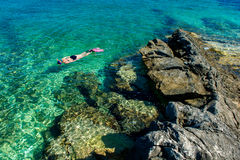 Mulher bonita no biquini que mergulha através da água de turquesa na costa Foto de Stock Royalty Free