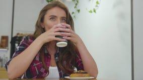 Mulher bonita no café bebendo do café com sobremesa filme