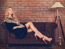 Mulher bonita no casaco de pele que senta-se no sofá Fotografia de Stock Royalty Free