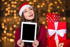 Mulher bonita no chapéu de Papai Noel com a tela vazia da tabuleta Fotografia de Stock