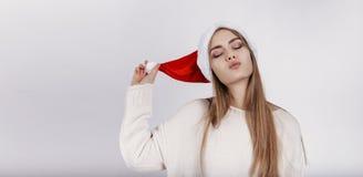 Mulher bonita no chapéu de Santa que tenta beijá-lo imagem de stock